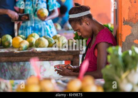 Woman stallholder using her mobile phone, Port Vila Fruit and Vegetable Market, late afternoon light. Vanuatu. - Stock Photo