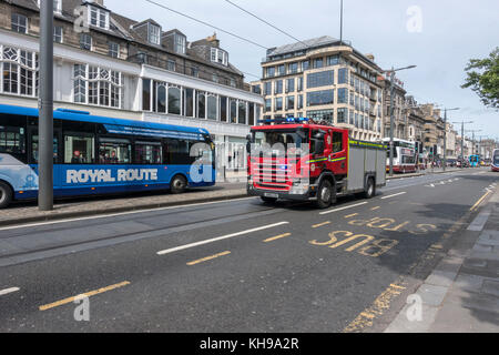 A Scottish Fire and Rescue Service Fire Truck Responding To An Emergency Call Driving On Princes Street Edinburgh - Stock Photo