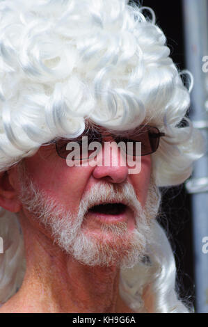 Male performer with a beard and wearing sunglasses and  a white wig on the Royal Mile during the Edinburgh International - Stock Photo