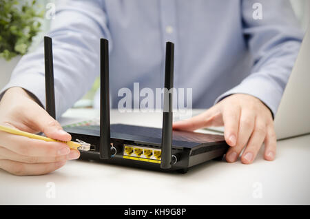 Man plugs Ethernet cable into router. router wireless wire broadband on ethernet cable diagram, usb plug wiring, cat 6 plug wiring, ethernet cable power, network plug wiring,