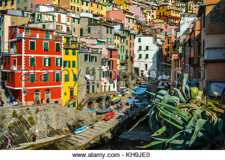 The colorful village of Riomaggiore in Cinque Terre on the Ligurian coast of Italy on a warm summer day with boats - Stock Photo