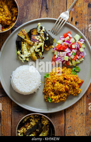 Indian meal with masoor dal - lentil curry, dahi baingan, rice and salad - Stock Photo