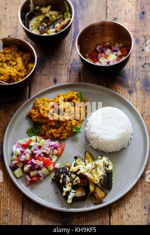 Indian meal with masoor dal - lentil curry, dahi baingan, rice and salad - Stock Photo