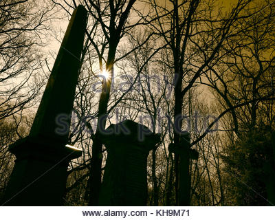 Highgate Cemetery London grave stone, cross and monument silhouetted in the trees - Stock Photo