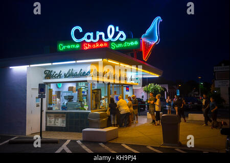 Fredericksburg, VA, USA - August 29, 2017: Line of people at Carl's vintage ice cream parlor with neon lights. - Stock Photo