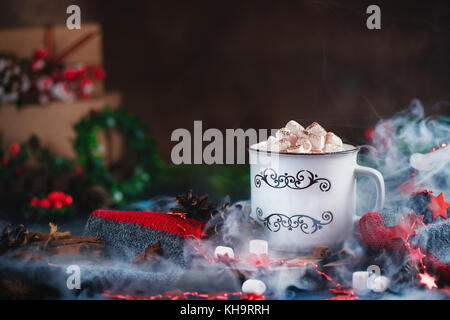 Hot chocolate with marshmallows in a cozy enamel mug with steam and Christmas decorations - Stock Photo
