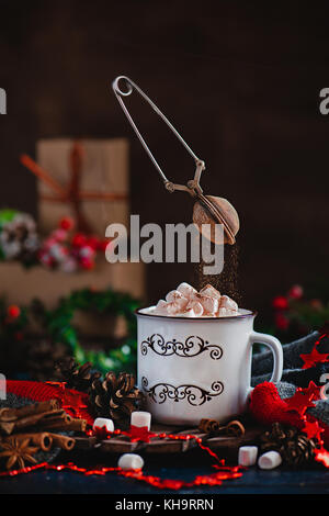 Hot chocolate with marshmallows and flying cocoa powder in Christmas scene with gifts. Action photography with flying - Stock Photo