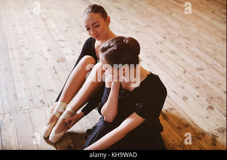 two ballerinas talking and smiling sitting on a wooden floor - Stock Photo