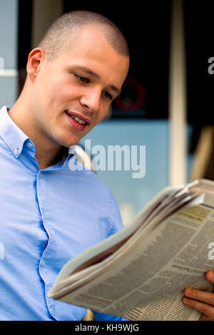 Portrait of handsome and positive businessman while standing in front of office building and reading the newspaper - Stock Photo