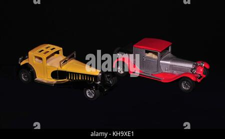 Two vintage cars models arranged to create innovative image in black background - Stock Photo