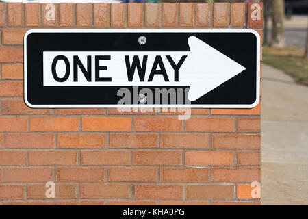 one way street sign affixed to a brick wall - Stock Photo