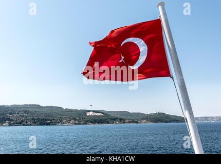 Turkish flag and Dur Yolcu memorial on background in Kilitbahir District,Canakkale,Turkey - Stock Photo
