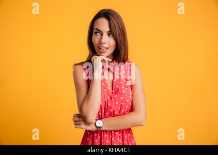 Photo of smiling young woman in red dress touching her chin, looking aside, isolated on yellow background - Stock Photo