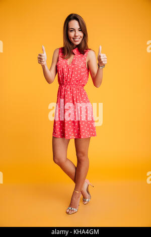 Full-length portrait of young happy woman standing with crossed legs showing thumbs up gesture, looking at camera, - Stock Photo