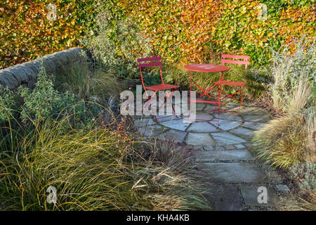 Small garden patio area with paving slabs and dining table and chairs, autumn, England, UK - Stock Photo