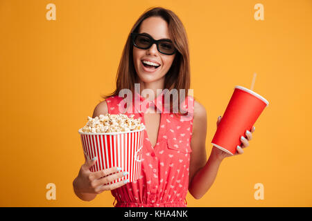 Happy brunette woman in dress and eyeglasses preparing to watch the film while holding popcorn and soda over yellow background