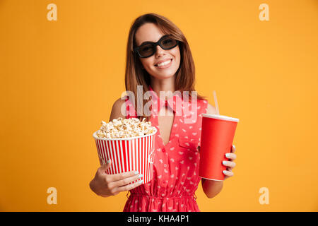 Pleased brunette woman in dress and eyeglasses preparing to watch the film while holding popcorn and soda over yellow background