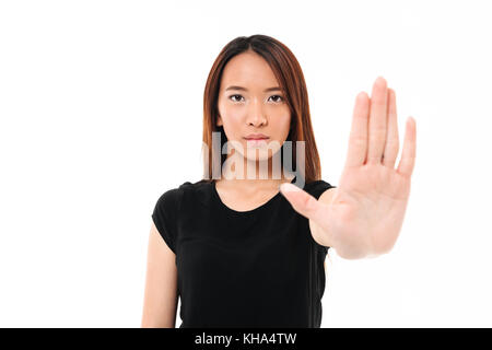 Portrait of serious asian woman standing with outstretched hand showing stop gesture isolated over white background - Stock Photo