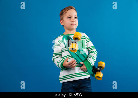 Picture of Young boy holding skateboard and looking aside over blue background - Stock Photo