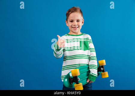 Smiling young boy holding skateboard and showing thumb up at camera over blue background - Stock Photo