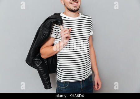Cropped image of smiling man holding his jacket on shoulder over gray background - Stock Photo