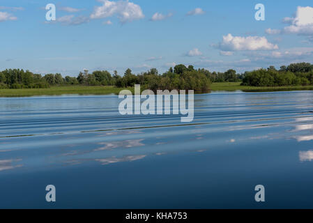 The picturesque landscape with green bushes, trees, meadows and clouds reflected in the water of the lake with a - Stock Photo