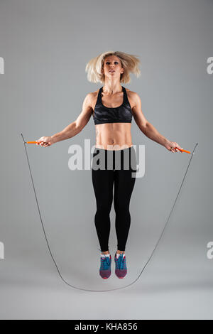 Full length portrait of a concentrated muscular adult sportswoman jumping on a skipping rope isolated over gray - Stock Photo