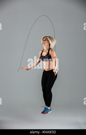 Full length portrait of a muscular adult sportswoman jumping on a skipping rope isolated over gray background - Stock Photo
