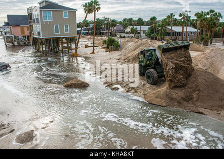 A member of the South Carolina Army National Guard dumps sand while cleaning up after Hurricane Matthew at Edisto - Stock Photo