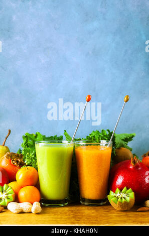 Freshly blended fruit smoothies of various colors and tastes in glass  in wooden tray. Yellow, green. on wooden - Stock Photo