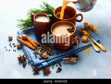 Pouring Masala tea chai latte traditional hot Indian teatime ceremony sweet milk with spices, herbs organic infusion - Stock Photo