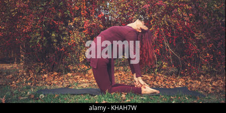 Girl on a bright autumn day practicing yoga outdoors, doing camel pose (ustrasana) - Stock Photo