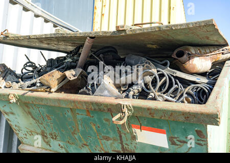 Collected scrap metal in rusty container - Stock Photo
