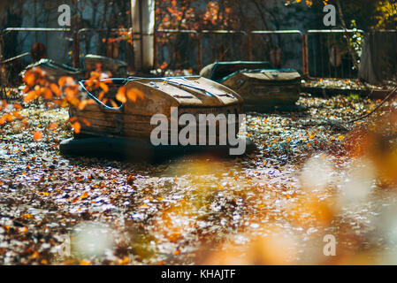 A forgotten bumper car lies amongst autumn leaves in the infamous abandoned theme park in Pripyat, near Chernobyl, - Stock Photo