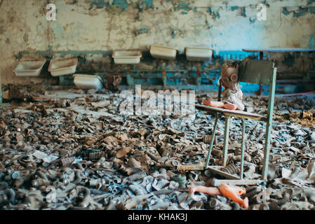 A child's doll is propped up on a chair in a sea of children's gas masks leftover from the Cold War in an abandoned - Stock Photo