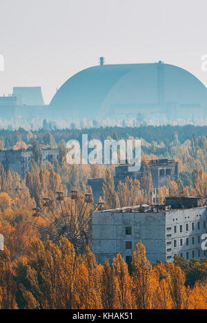 The dome covering the Chernobyl power plant looms over the abandoned town of Pripyat's theme park ferris wheel peeking - Stock Photo