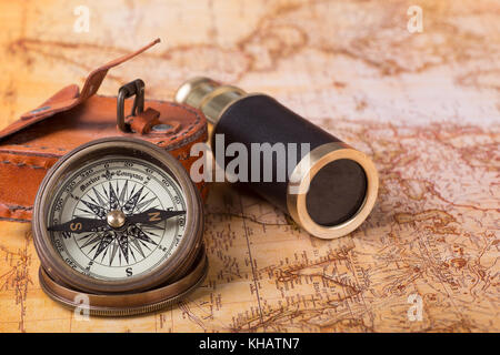 Brass compass and telescope on a world map - Stock Photo