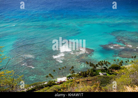 Beautiful view from the top of the Diamond Head crater over some residences and some of the coastal coral reefs - Stock Photo