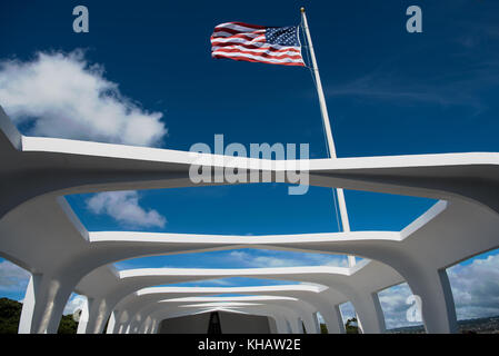 The Star-Spangled Banner flies above the USS Arizona Memorial at Pearl Harbor, which the resting place of 1,102 - Stock Photo