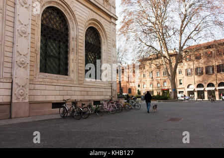 BOLOGNA, ITALY -FEBRUARY 08, 2017: Bicycle parking, a resident of Bologna, walking with a dog - Stock Photo