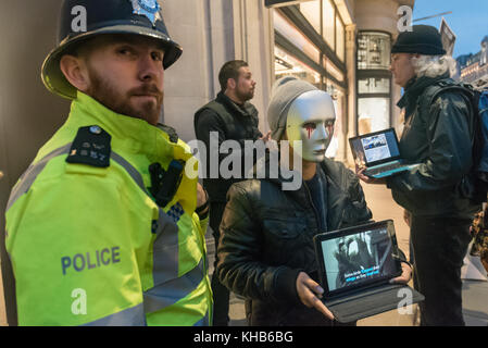 London, UK. 14th November 2017. A police officer stands next to protesters showing a film about animal cruelty as - Stock Photo
