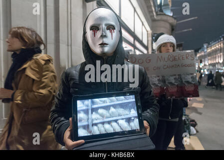 London, UK. 14th November 2017. A woman wears a mask with blood dripping down it and holds a tablet showing birds - Stock Photo