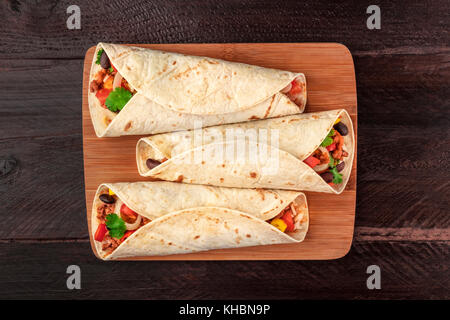 An overhead photo of Mexican burritos with beef, rice, black beans, vegetables, and chili peppers, with a place - Stock Photo
