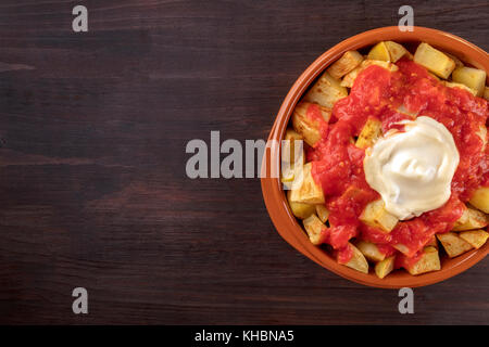 An overhead closeup of a bowl of patatas bravas, traditional Spanish dish of fried potatoes with two sauces, on - Stock Photo
