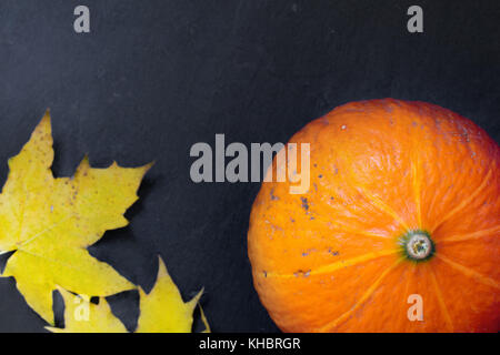 pumpkin with colorful autumn leaves - Stock Photo