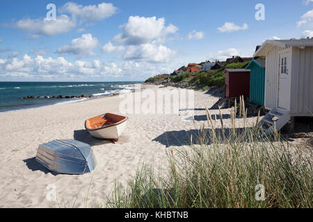 Boats and beach huts on white sand beach with town behind, Tisvilde, Kattegat Coast, Zealand, Denmark, Europe - Stock Photo