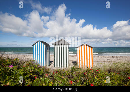 Colourful beach huts on pebble beach with blue sea and sky with clouds, Rageleje Strand, Kattegat Coast, Zealand, - Stock Photo