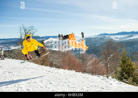 Bukovel, Ukraine - December 22, 2016: Men boarders jumping on his snowboard against the backdrop of mountains, hills - Stock Photo