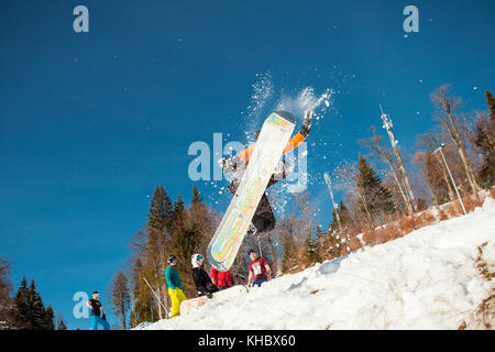 Bukovel, Ukraine - December 22, 2016: Man boarder jumping on his snowboard against the backdrop of mountains, hills - Stock Photo