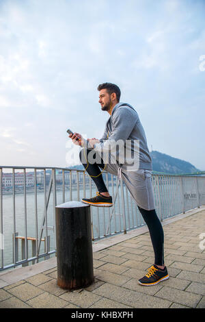 A handsome young man putting his leg up and leaning on it while using his phone at the riverside - Stock Photo